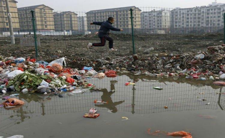 Menino tenta evitar  poça d'agua pulando em lixo