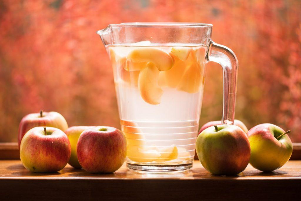 Mesa com maçãs e uma jarra com vinagre de maça
