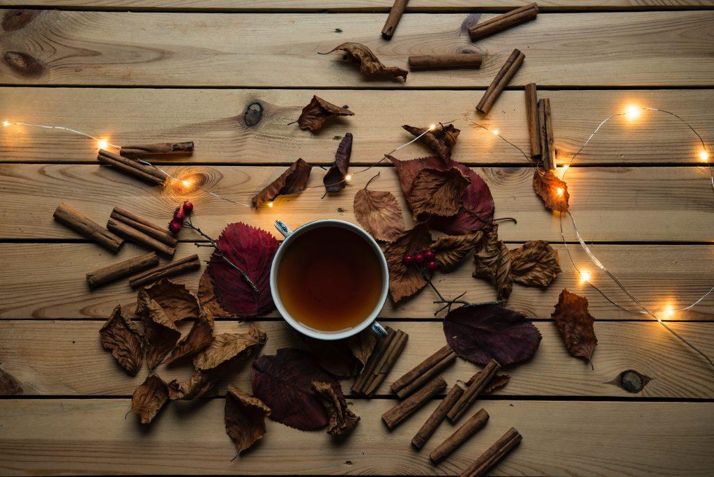Mesa vista de cima com uma xícara com chá de canela