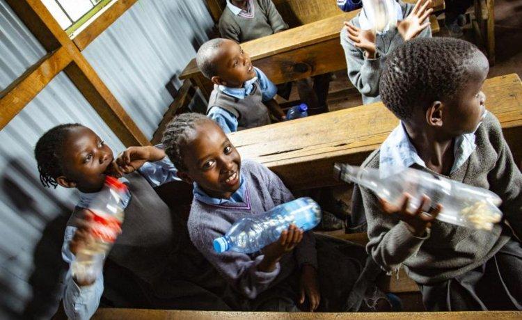Crianças no campo de Kibera, no Quênia, têm aula de música especial, que combina o ensino de instrumentos com educação ambiental. Foto: ONU Meio Ambiente/Duncan Moore
