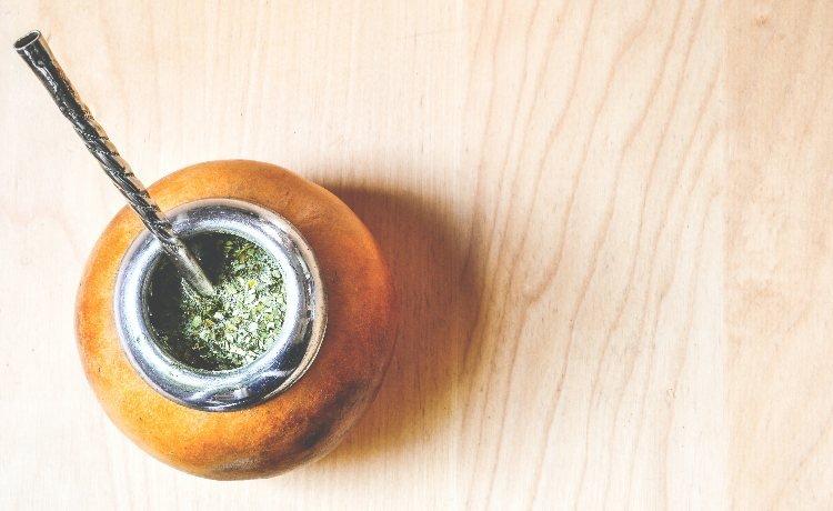Fotografia colorida de uma bomba de chimarrão cor caramelo com ervas e canudo de inox