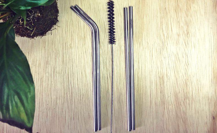 Fotografia colorida em ambiente interno de dois canudos curvados e dois canudos retos de inox com uma escova higienica entre os dois.